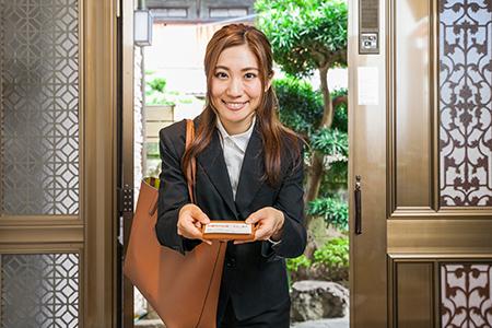 笑顔で玄関にたつ女性査定員
